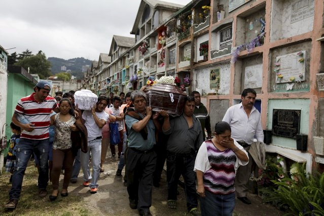 Relatives attend the funeral of two victims of a mudslide in Santa Catarina Pinula, on the outskirts of Guatemala City, October 3, 2015. Rescue workers scrabbled through earth and rubble on Saturday in search of survivors of a massive landslide in Guatemala that killed at least 48 people, even as hopes began to fade for hundreds of others still missing. (Photo by Jose Cabezas/Reuters)