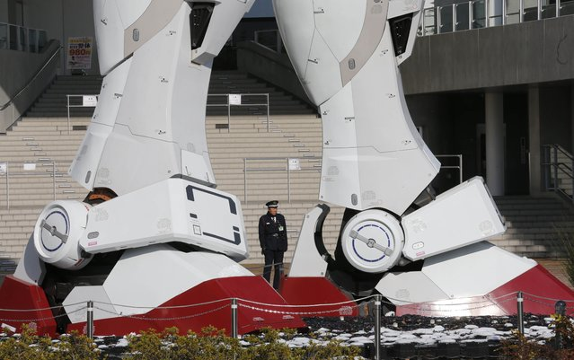A security officer stands at the legs of a giant model of Japan's popular robot animation character Gundam in Tokyo,Tuesday, January 15, 2013. (Photo by Koji Sasahara/AP Photo)