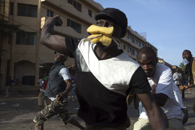 Anti-government protesters throw rocks at police in Ouagadougou, capital of Burkina Faso, October 30, 2014. (Photo by Joe Penney/Reuters)