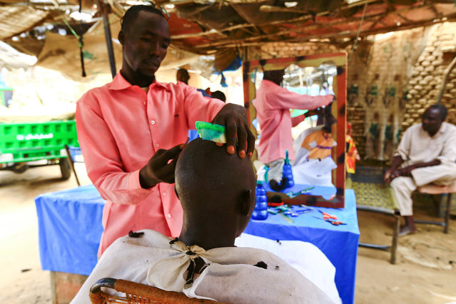 A barber attends to a client in Abu Shock IDPs camp in Al Fashir, capital of North Darfur, Sudan, September 6, 2016. (Photo by Mohamed Nureldin Abdallah/Reuters)