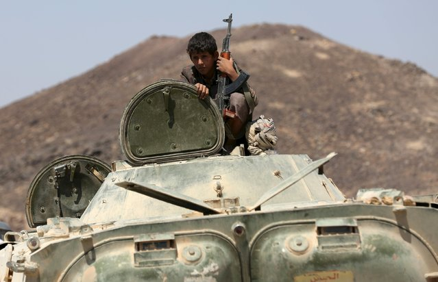 A young tribal fighter loyal to Yemen's government rides in an armoured vehicle at the frontline of fighting against Houthi militants in the central province of Marib October 7, 2015. (Photo by Reuters/Stringer)