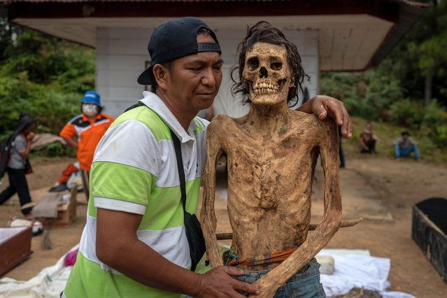 """Roni Pasang hugged his cousin's body Sampe during a traditional ritual called """"Manene"""" in Panggala, Nort Toraja, South Sulawesi, Indonesia, Tuesday, August 25th 2020. (Photo by Hariandi Hafid/ZUMA Wire/Rex Features/Shutterstock)"""