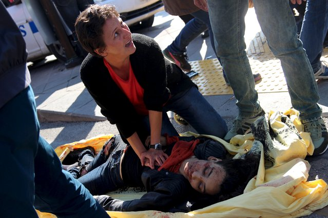 A woman helps an injured woman after an explosion during a peace march in Ankara, Turkey, October 10, 2015. At least one explosion shook a road junction in the centre of the Turkish capital Ankara on Saturday, causing many casualties including fatalities, local media said. The state-run Anadolu Agency said there were reports that the blast was caused by a suicide bomber, but the source of those reports was unclear. (Photo by Tumay Berkin/Reuters)