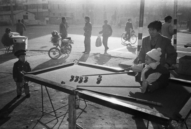 A child sitting on a roadside snooker pool plays with her mother in Beijing in 1983. (Photo by Reuters/China Daily)
