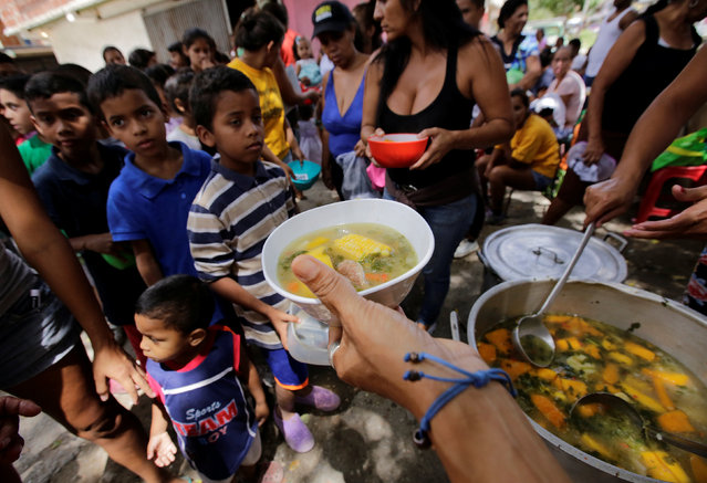 Children queue wait to receive free food which was prepared by residents and volunteers on a street in the low-income neighborhood of Caucaguita in Caracas, Venezuela September 17, 2016. (Photo by Henry Romero/Reuters)