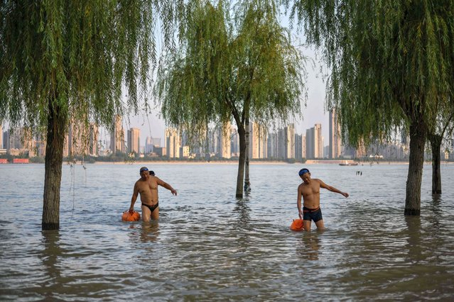 In this photo taken on September 5, 2020, men return from swimming in the Yangtze River in Wuhan, China's central Hubei province. China is recasting Wuhan as a heroic coronavirus victim and trying to throw doubt on the pandemic's origin story as it aims to seize the narrative at a time of growing global distrust of Beijing. (Photo by Hector Retamal/AFP Photo)