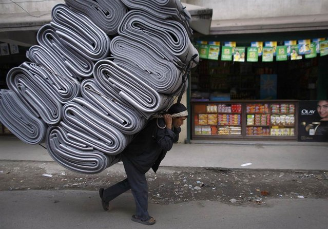 A Nepalese porter carries a pile of mats in Kathmandu on February 21, 2013. Most porters earn less than $3 for carrying their load about a half mile. (Photo by Navesh Chitrakar/Reuters)