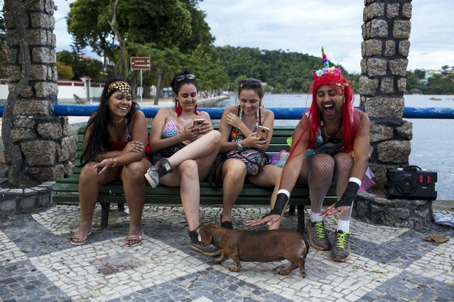 """Revellers celebrate the pre-carnival street parade of the """"Perola da Guanabara"""" (Guanabara Pearl) street carnival group at Paqueta Island, on Guanabara Bay in Rio de Janeiro, Brazil, on February 3, 2018. (Photo by Mauro Pimentel/AFP Photo)"""