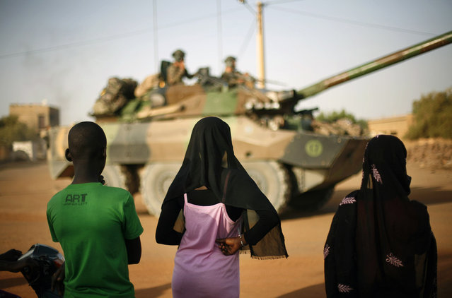 Malian teenagers watch a convoy of French military vehicles pass through Gao, on February 19, 2013. (Photo by Jerome Delay/AP Photo/The Atlantic)