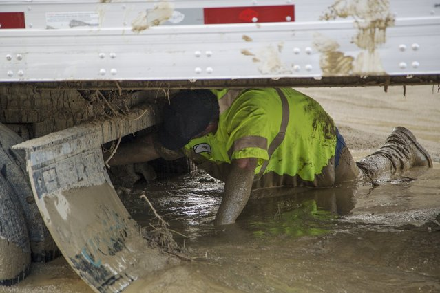 A worker crawls to connect chains to pull on a truck mired in mud and debris on State Route 58 near Tehachapi, California, about 60 miles (97 km) outside of Los Angeles October 17, 2015. (Photo by David McNew/Reuters)