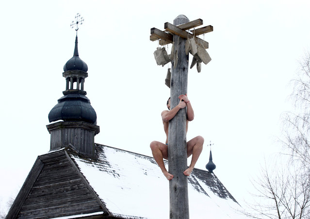 A man climbs up a wooden pole to get a prize during celebration of Maslenitsa, or Pancake Week, in Belarusian state museum of folk architecture and rural lifestyle near the village Aziarco, Belarus, February 17, 2018. (Photo by Vasily Fedosenko/Reuters)