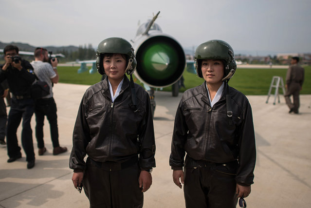 """North Korean pilots Jo Kyum-Hyang (R) and Rim Sol (L), known in North Korea as the """"Flowers of Sky"""", pose for photos during the second day of the Wonsan Friendship Air Festival in Wonsan on September 25, 2016. (Photo by Ed Jones/AFP Photo)"""