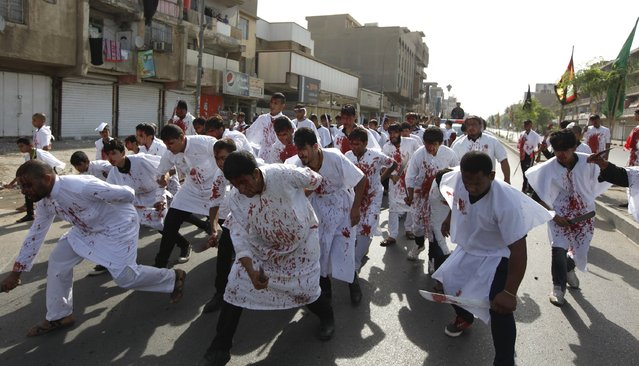 Iraq Shi'ite Muslim men bleed as they gash their foreheads with swords and beat themselves while commemorating Ashura in Baghdad, October 24, 2015. (Photo by Ahmed Saad/Reuters)