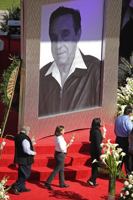 People walk past a giant picture of the late screenwriter Roberto Gomez Bolanos before the start of a mass held in his honour at the Azteca stadium in Mexico City November 30, 2014. (Photo by Tomas Bravo/Reuters)