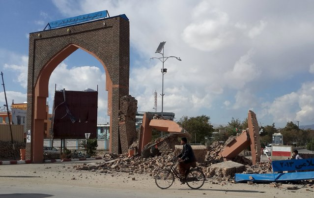 A man rides his bicycle next to damaged structures, after an earthquake in Ghazni, Afghanistan October 26, 2015. (Photo by Reuters/Stringer)
