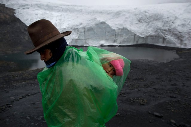 Fausta Ortiz, 38, Pastoruri's glacier guardian, stands guard while carrying her daughter Lisoyun, 2, in Huaraz, Peru, Thursday, December 4, 2014. (Photo by Rodrigo Abd/AP Photo)