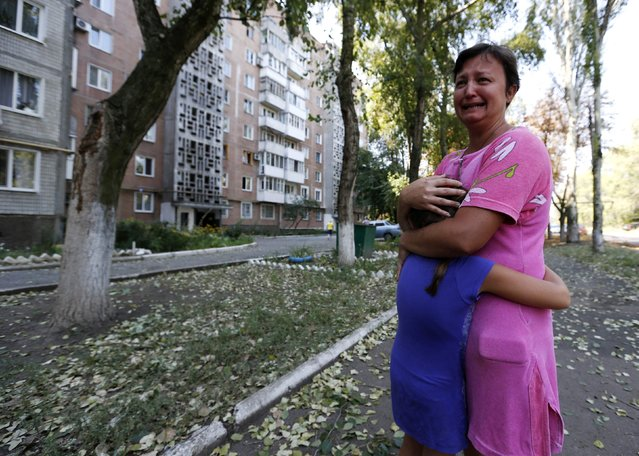 A woman reacts near a damaged multi-storey block of flats following what locals say was recent shelling by Ukrainian forces in Donetsk, in this August 13, 2014 file photo. (Photo by Sergei Karpukhin/Reuters)