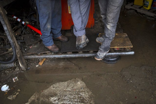 Workers stand on a platform in a flooded workshop in the Willets Point area of Queens in New York October 28, 2015. (Photo by Andrew Kelly/Reuters)