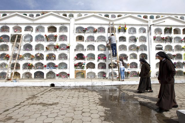 Nuns walk in front of graves at a cemetery, known for its topiary art, during the observance of the Day of the Dead, in Tulcan, Ecuador November 2, 2015. (Photo by Guillermo Granja/Reuters)