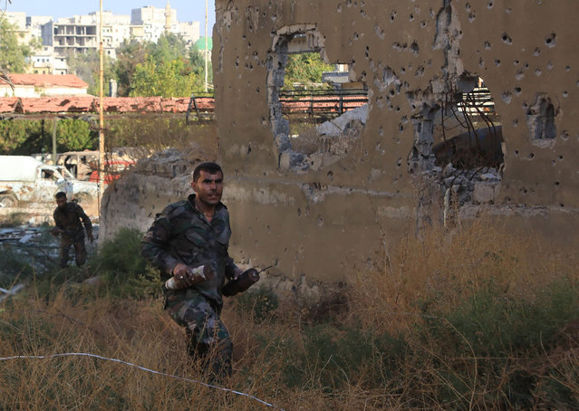 "A Syrian pro-government soldier carries home-made bombs as they advance in Aleppo's rebel-held Bustan al-Basha neighbourhood on October 6, 2016. ""Syrian regime forces advanced from the city centre north into (rebel-held) Bustan al-Basha, and seized a large athletic complex there"", the UK-based Syrian Observatory for Human Rights said. This was the first time the regime had entered the district since 2013 and there had been fierce clashes, they added. This was the first time the regime had entered the district since 2013 and there had been fierce clashes, he added. (Photo by George Ourfalian/AFP Photo)"