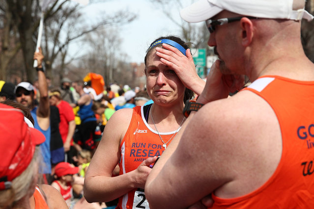 A runner reacts near Kenmore Square after two bombs exploded during the 117th Boston Marathon on April 15, 2013 in Boston, Massachusetts. (Photo by Alex Trautwig)