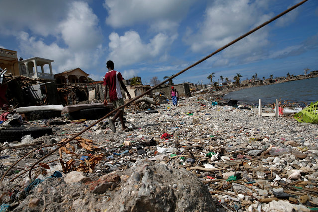 People walk on a beach near destroyed houses after Hurricane Matthew hit Jeremie, Haiti, October 10, 2016. (Photo by Carlos Garcia Rawlins/Reuters)
