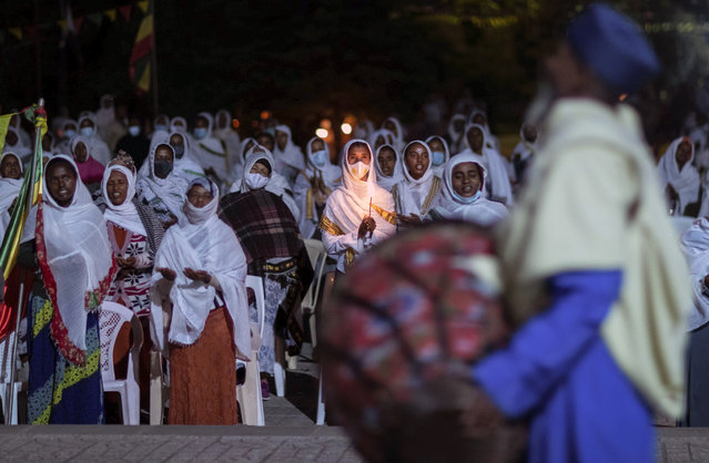 """Ethiopian Orthodox Christians light candles and pray for peace during a church service at the Medhane Alem Cathedral in the Bole Medhanealem area of the capital Addis Ababa, Ethiopia Thursday, November 5, 2020. Ethiopia's powerful Tigray region asserts that fighter jets have bombed locations around its capital, Mekele, aiming to force the region """"into submission"""", while Ethiopia's army says it has been forced into an """"unexpected and aimless war"""". (Photo by Mulugeta Ayene/AP Photo)"""