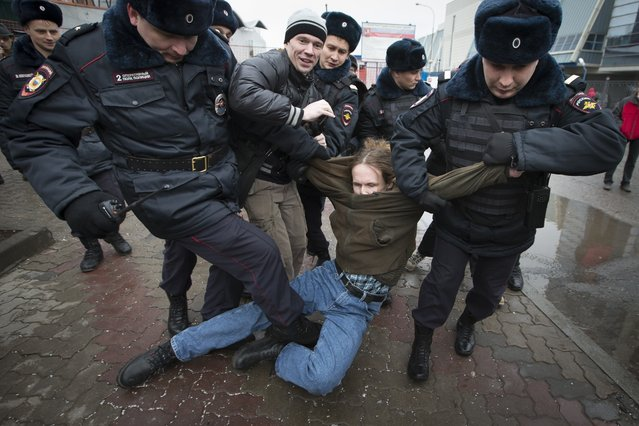 Russian police officers detain protesters who were going planning on asking Vladimir Putin their own questions at today's news conference,  in Moscow, Russia, Thursday, December 18, 2014. The Russian economy will rebound and the ruble will stabilize, Russian President Vladimir Putin said Thursday at his annual press conference, he also said Ukraine must remain one political entity, voicing hope that the crisis could be solved through peace talks. (Photo by Alexander Zemlianichenko/AP Photo)