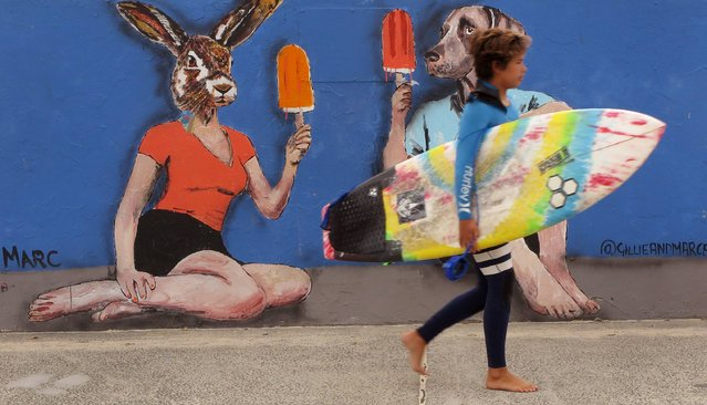 A young surfer walks past street art on the way to surf at Sydney's iconic Bondi Beach on October 3, 2016. (Photo by William West/AFP Photo)