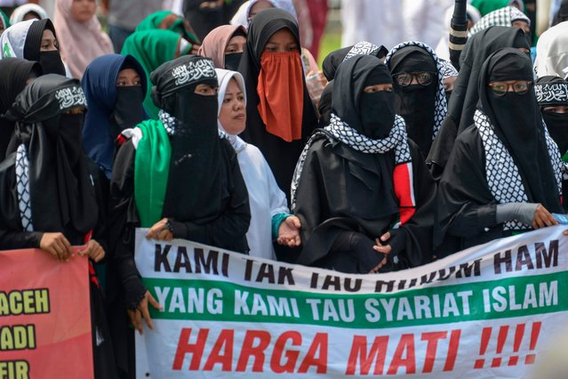 Supporters of an Indonesian hardline Muslim group gather to protest in Banda Aceh on April 19, 2018, against a new regulation that will see criminals flogged only behind prison walls. (Photo by Chaideer Mahyuddin/AFP Photo)