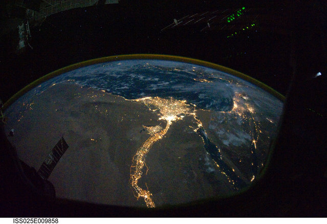 A night time photograph made by an International Space Station Expedition 25 crewmember shows the bright lights of Cairo and Alexandria, Egypt on the Mediterranean coast as well as the Nile River and its delta which stand out clearly in this image released by NASA and taken October 28, 2010. (Photo by Reuters/NASA)