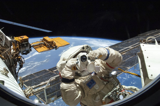 Russian cosmonaut taking a photograph during extravehicular activity (EVA) on the International Space Station on August 18, 2014. (Photo by NASA/SPL/Barcroft Media)