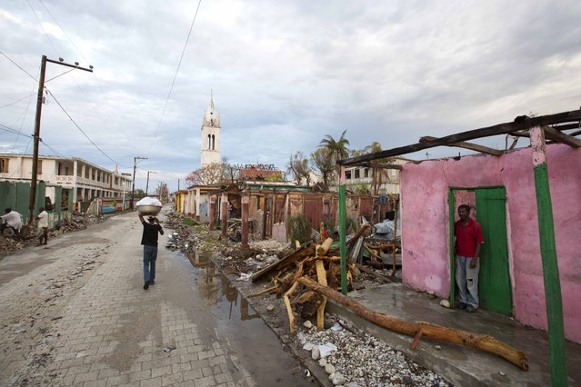 In this Wednesday, October 19, 2016 photo, Clony Toussaint stands in the doorway of his home, damaged by Hurricane Matthew, in Port-a-Piment, a district of Les Cayes, Haiti. Wednesday Oct. 19, 2016. Government personnel and an army of international aid workers are delivering more relief supplies to people, but local authorities say it is falling well short of meeting desperate needs. (Photo by Dieu Nalio Chery/AP Photo)