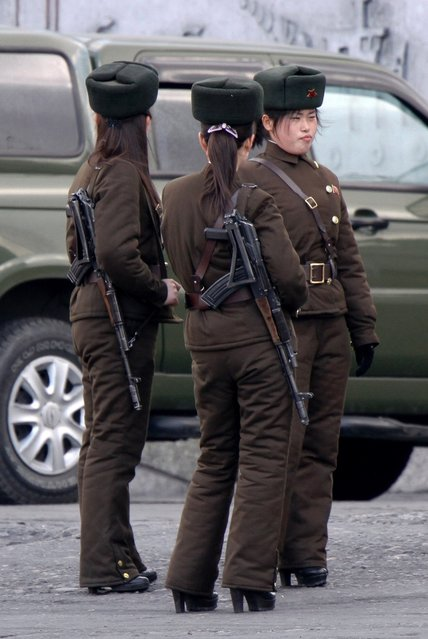 In this Thursday, April 11, 2013 photo, North Korean female soldiers stand watch on the river bank of the North Korean town of Sinuiju, opposite to the Chinese border city of Dandong. (Photo by AP Photo)