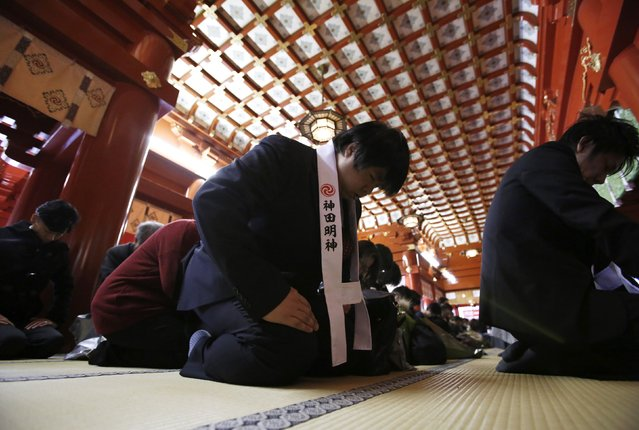 Businessmen wearing Shinto vests offer prayers before the altar at the start of the new business year at Kanda Myojin Shrine in Tokyo January 5, 2015. More than 3,100 company representatives visit the shrine on the first business day of the new year, according to the shrine, to seek good luck and prosperous businesses. (Photo by Toru Hanai/Reuters)