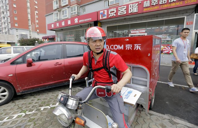 Richard Liu, CEO and founder of China's e-commerce company JD.com, rides an electric tricycle as he leaves a delivery station to deliver goods for customers to celebrate the anniversary of the founding of the company, in Beijing, in this June 16, 2014 file photo.  China's second-largest e-commerce company JD.com Inc said it has sent a letter of complaint to a Chinese antitrust regulator and formally requested an investigation into rival Alibaba Group Holding. (Photo by Jason Lee/Reuters)