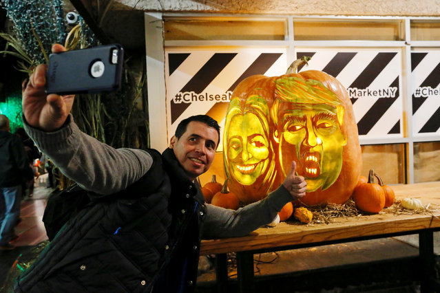 A man takes a selfie next to a giant pumpkin created by Master Carver Hugh McMahon with the faces of 2016 Democratic nominee Hillary Clinton and Republican presidential nominee Donald Trump at Chelsea Market in New York, U.S., October 28, 2016. (Photo by Eduardo Munoz/Reuters)