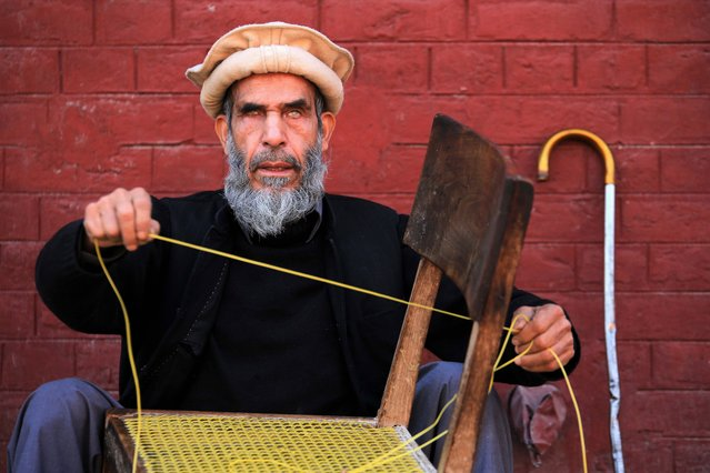 """A visually impaired man weaves a chair at the Government School and Institute for the Blind, in Peshawar, Pakistan, on the eve of the International Day of People with Disabilities, 02 December 2020. According to reports there are approximately five million people falling into the category of having some form of disability in Pakistan. The International Day of Disabled Persons, annually celecrated on 03 December, was proclaimed by the UN General Assembly resolution 47/3 in 1992 and aims to """"promote the rights and well-being of persons with disabilities in all spheres of society and development"""" as the UN says on its website. (Photo by Bilawal Arbab/EPA/EFE)"""