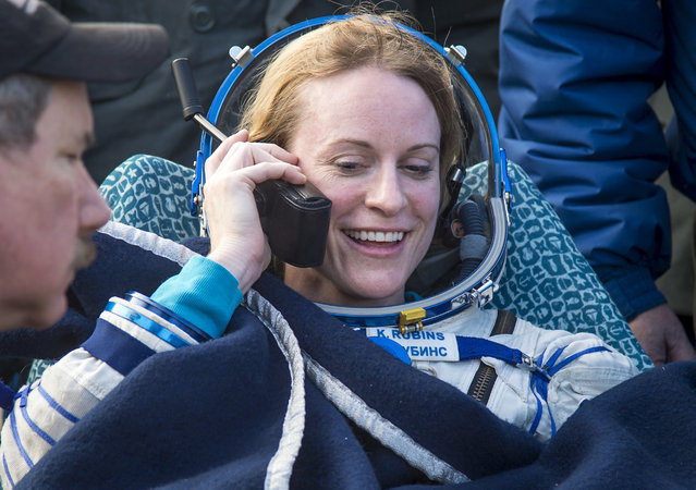 In this photo released by NASA, NASA astronaut Kate Rubins talks to her family via satellite phone shortly after she is helped out of the Soyuz MS-01 spacecraft along with Russian cosmonaut Anatoly Ivanishin of Roscosmos and astronaut Takuya Onishi of the Japan Aerospace Exploration Agency (JAXA) who landed in a remote area near the town of Zhezkazgan, Kazakhstan Sunday, October 30, 2016. (Photo by Bill Ingalls/NASA via AP Photo)