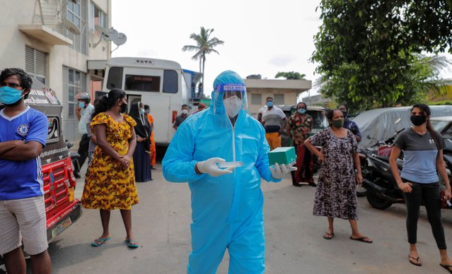 A Sri Lankan health official carries a test kit to inspect residents at a housing complex as they prepare to collect swab samples to test for COVID-19 in Colombo, Sri Lanka, Monday, November 23, 2020. (Photo by Eranga Jayawardena/AP Photo)