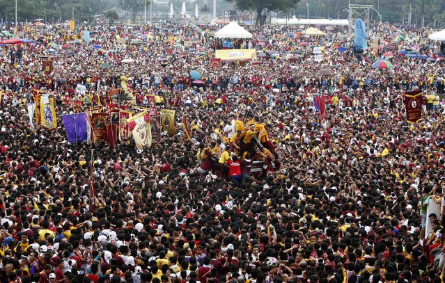 The carriage carrying the Black Nazarene is surrounded by devotees during an annual procession in Manila, January 9, 2015. (Photo by Erik De Castro/Reuters)