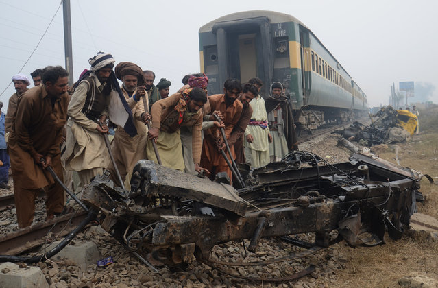 Men try to clear the tracks after the Karachi express (Night Coach) and oil container accident in Raiwind ''Bachoki ''47 km from Lahore, Raiwind, Punjab, Pakistan on November 30, 2015. At least five people were dead and 17 injured. (Photo by Rana Sajid Hussain/Pacific Press via ZUMA Wire)