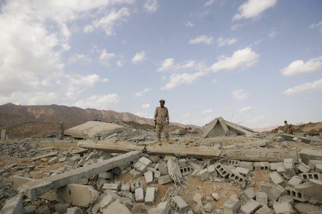 An army officer stands on the ruins of a police barracks, which was bombed by al Qaeda insurgents, at al-Mahfad, in the southern Yemeni province of Abyan May 23, 2014. (Photo by Khaled Abdullah/Reuters)