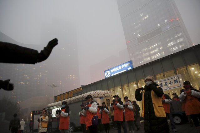 Volunteers exercise before delivering free food on an extremely polluted morning as hazardous, choking smog continues to blanket central Beijing, China December 1, 2015. (Photo by Damir Sagolj/Reuters)