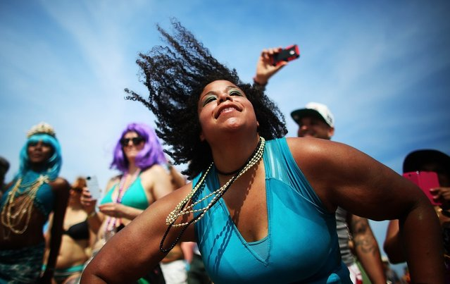 NEW YORK, NY - JUNE 22:  Revelers dance on the beach at the 2013 Mermaid Parade at Coney Island on June 22, 2013 in the Brooklyn borough of New York City. Coney Island was hard hit by Superstorm Sandy but parade organizers, whose offices were flooded, were able to raise $100,000 on Kickstarter to fund the parade. The Mermaid Parade began in 1983 and features participants dressed as mermaids and other sea creatures while paying homage to the former tradition of the Coney Island Mardi Gras, which ran annually in the early fall from 1903-1954.  (Photo by Mario Tama/Getty Images)