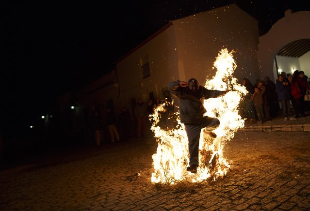 "A man jumps over a bonfire during the ""Luminarias"" annual religious celebration on the eve of Saint Anthony's Day in the village of Alosno, southwest Spain, January 16, 2015. (Photo by Marcelo del Pozo/Reuters)"