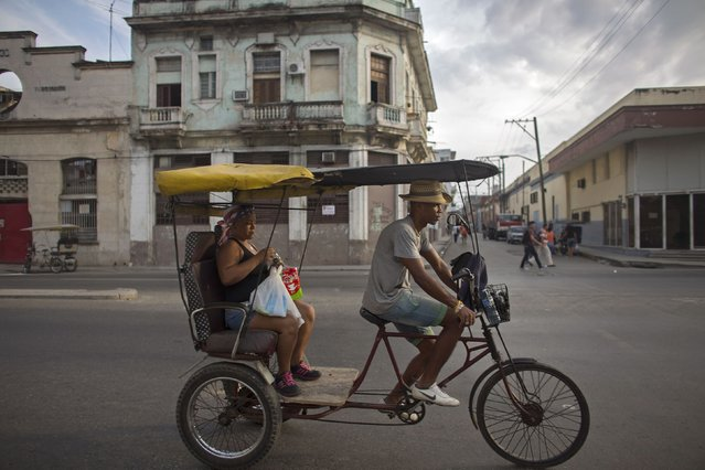 A bike taxi driver rides with a passenger in downtown Havana January 9, 2015. From bus drivers to bartenders and ballet dancers, many Cubans are already imagining a more prosperous future after the United States said it will put an end to 50 years of conflict with the communist-run island. (Photo by Alexandre Meneghini/Reuters)