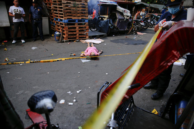 Policemen investigate near the body of a woman killed by unknown gunmen at the market in a port area of Manila, Philippines October 28, 2016. (Photo by Damir Sagolj/Reuters)