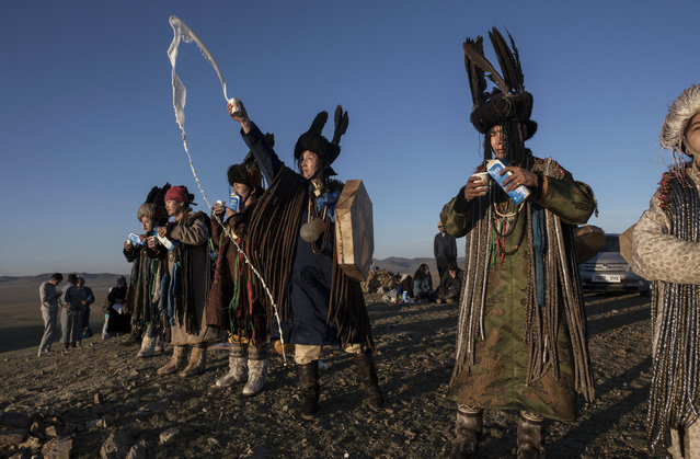 Mongolian Shamans or Buu, throw milk as an offering during a sun ritual ceremony to mark the period of the Summer Solstice in the grasslands at sunrise on June 22, 2018 outside Ulaanbaatar, Mongolia. (Photo by Kevin Frayer/Getty Images)