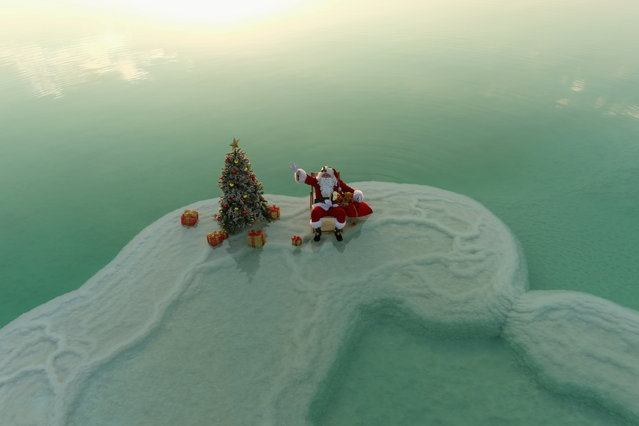 An aerial view shows Issa Kassissieh, wearing a Santa Claus costume, and sitting next to a Christmas tree while posing for a picture on a salt formation in the Dead Sea, in an event organised by Israel's tourism ministry, as Israel gears up for the holiday season, amid the coronavirus disease (COVID-19) crisis, near Ein Bokeq, Israel on November 15, 2020. (Photo by Ilan Rosenberg/Reuters)